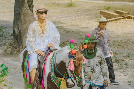 RATCHABURI-Thailand, April 14, 2019 : Unidentified Young man riding horse with music band in ordination ceremony in buddhist at local road on April 14,2019 in Ratchaburi, Thailand. Editöryel