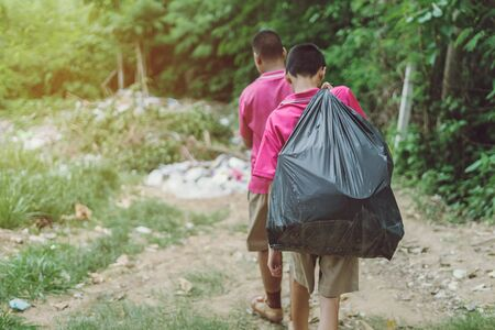 Male Students help to remove rubbish from the classroom to pile waste. Selective focus on black garbage bag. Banque d'images