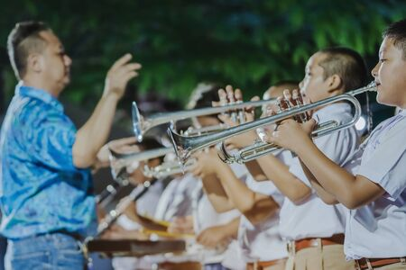 KANCHANABURI-THAILAND, April 12 : Unidentified Male student with friends blow the trumpet with the band for performance on stage at school on april 12,2019 in Kanchanaburi, Thailand.