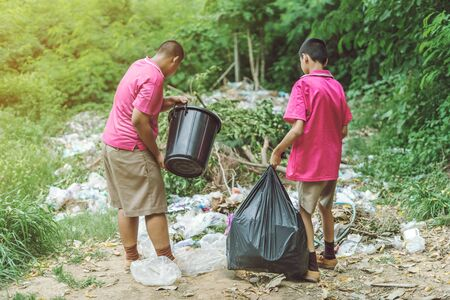 Male Students help to remove rubbish from the classroom to pile waste. Selective focus on black garbage bag. 版權商用圖片