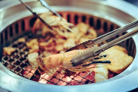 People grilling meat on a smokeless barbecue grill in a restaurant. Selective focus on tongs.