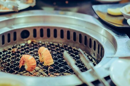 People grilling meat on a smokeless barbecue grill in a restaurant. Selective focus on shrimps.