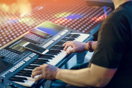 Musician play electronic keyboard synthesizers by using smartphone as guidelines for playing on the concert stage. Selective focus on smartphone.