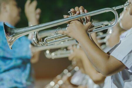 Un étudiant avec des amis souffle de la trompette avec le groupe pour se produire sur scène la nuit. Banque d'images