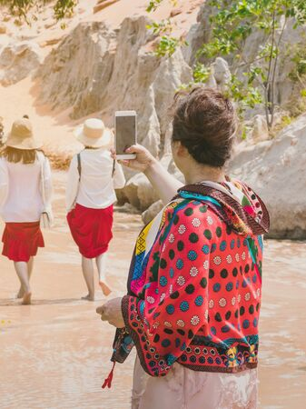 Back view of tourists walk on feet in the Red Stream ( it also named Fairy Stream) with Beautiful scenic landscape with red river, sand dunes and jungle. Tropical oasis scenery in Vietnam. Imagens