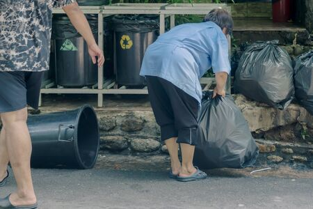 Female worker sort the garbage and packed in black bags for transportation convenience. Imagens