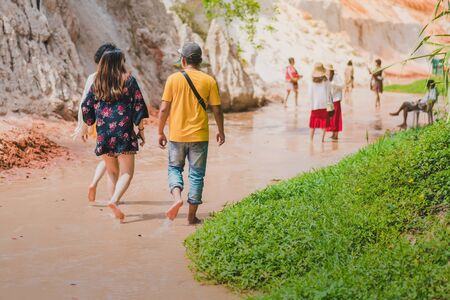 Back view of tourists walk on feet in the Red Stream ( it also named Fairy Stream) with Beautiful scenic landscape with red river, sand dunes and jungle. Tropical oasis scenery in Vietnam. Stock Photo