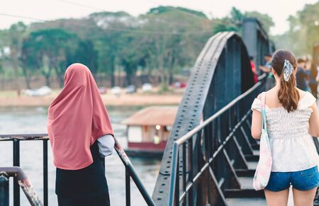 Back view of Muslim woman relax and admire the beautiful scenery in the evening on The Bridge of the River Kwai in Kanchanaburi, Thailand. Stock fotó