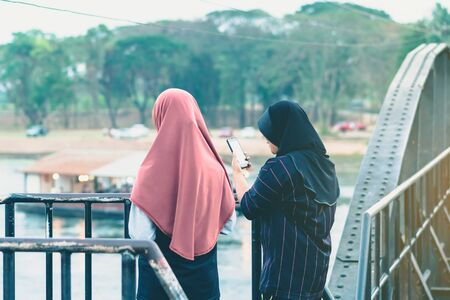 Back view of Muslim women relax and admire the beautiful scenery in the evening on The Bridge of the River Kwai in Kanchanaburi, Thailand.