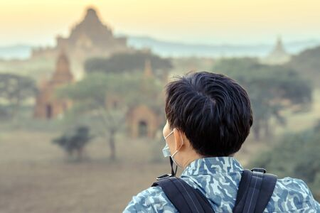 Back wiew of tourists admire and take photography while the sun sets at the ancient pagoda temples in the asian historic heritage city Bagan, Myanmar