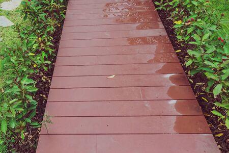 The reddish brown wooden walkway after rain in the garden.