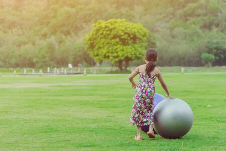 Happiness girl in the floral skirt relax and play with a big ball on green field in the public garden.