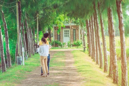 Couple walking and taking photos under the pine trees in the public park. Imagens