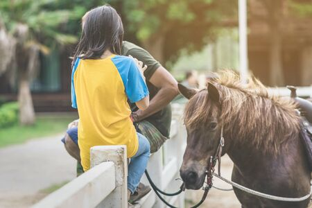 Girl in yellow and blue shirt use smartphone to take photos at the horse riding field in the evening.