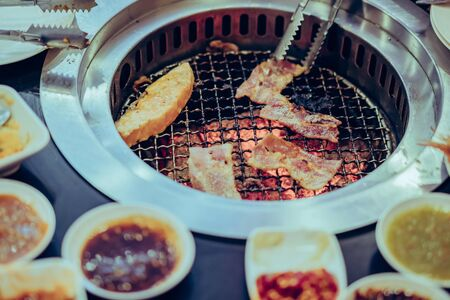 People grilling meat on a smokeless barbecue grill in a restaurant. Imagens