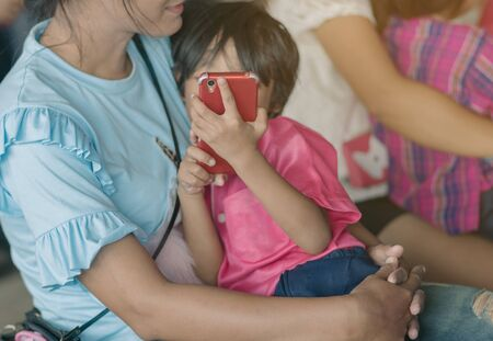 Mom is enjoying time with her daughter while she is using smartphone.