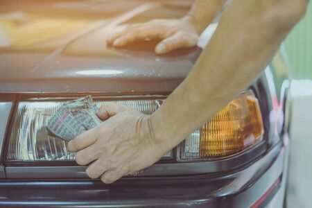 Close up to hand of male worker use wet newspapers to clean the glass part of the car. Selective focus on  newspaper.