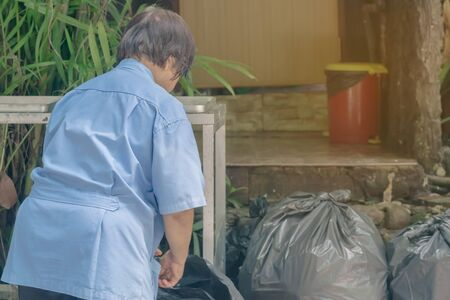 Female worker sort the garbage and packed in black bags for transportation convenience. 写真素材
