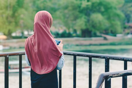 Back view of Muslim woman relax and admire the beautiful scenery in the evening on The Bridge of the River Kwai in Kanchanaburi, Thailand. Imagens