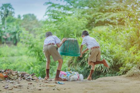 Male Students help to remove rubbish from the classroom to pile waste