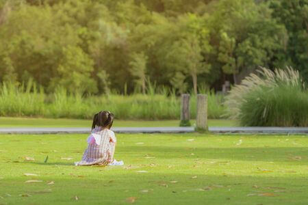 A little girl in a pink skirt enjoys a relaxing time playing on the green lawn at the public park in the evening.