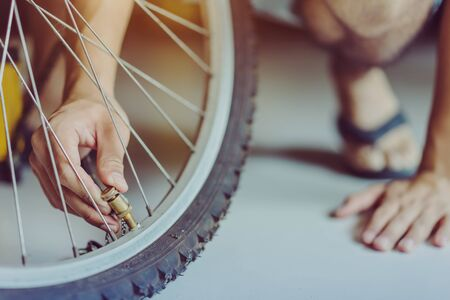 Close-up of a young man prepare to pumping the old bicycle wheel in his home. .