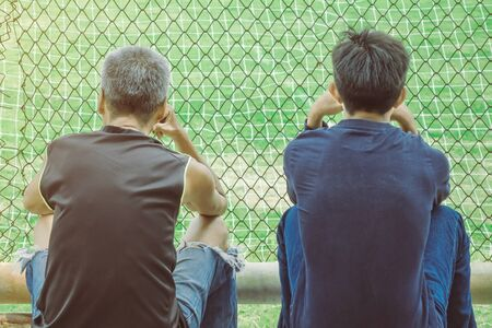 Back view of male parents cheering their childrens playing football in school. Stockfoto