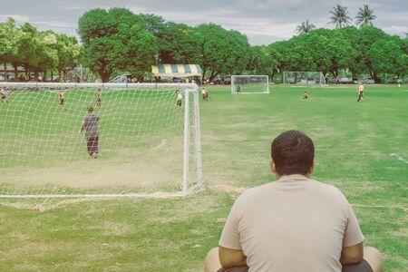 Back view of male parent cheering children playing football in school. Stockfoto