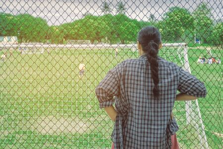 Back view of female parent cheering children playing football in school.