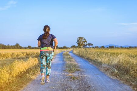 Back view of woman running and exercising on the path through the rice fields in the evening. 免版税图像