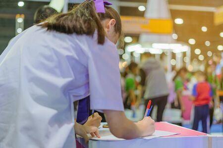 Female students answering questionnaires about visiting the exhibition