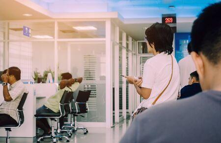 Rückansicht von Menschen, die bei Finanztransaktionen in der Bank sitzen und warten.
