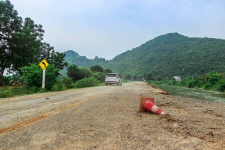 The old traffic cone falling on the road that was being repaired along the irrigation canal for agriculture. Stok Fotoğraf