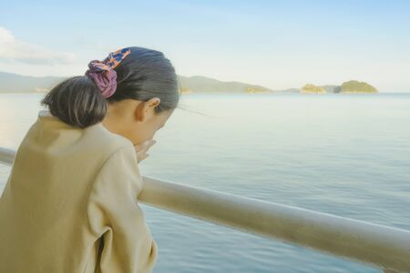 Asian young girl stands on baluster of ferry for relaxing and look at the ocean and island