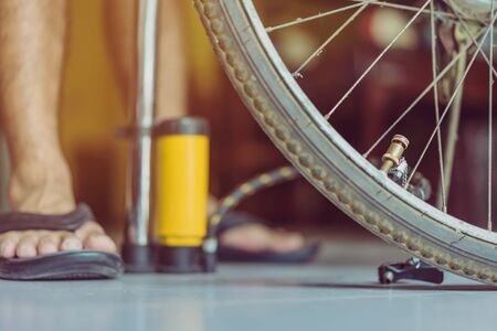Close-up of a young man prepare to pumping the old bicycle wheel in his home.