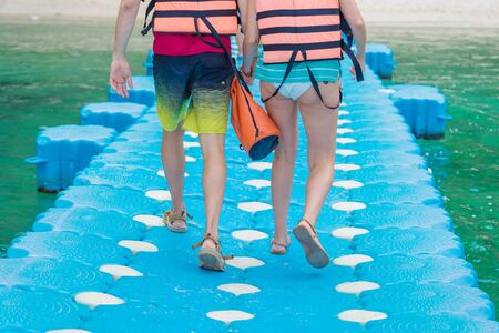 Lovers couple holding hands while walking on plastic pontoon walk way floating in the sea go to the beach. Banco de Imagens - 132126324