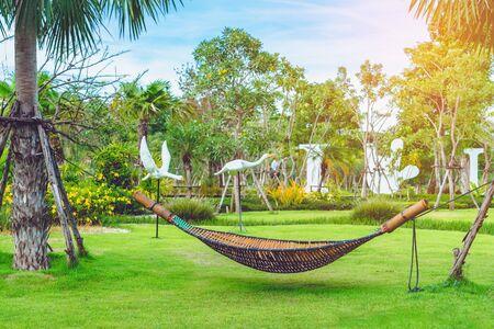 Bamboo wicker hammock hanging on tree for relaxing in the public garden.