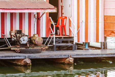 The old electricity generator for floating wooden raft house by using towing boat. Reklamní fotografie