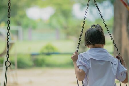 Back view of young girl sit on swing for wait her friend at the playground.
