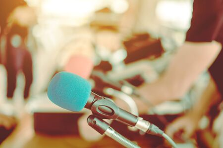 Two microphones with blue and red sponges placed on a stand with earphones on the table with blur image of the audio technician was installing and testing the sound system in the background.