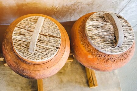 Row of earthen jars with wood lids and rough gray floor for water storage in Asian house. Selective focus on wood lids.