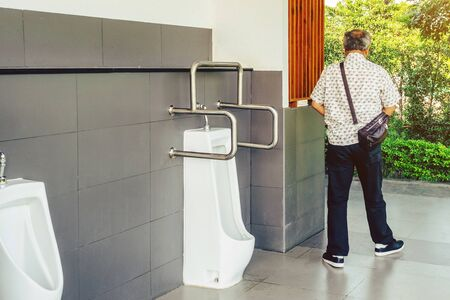 Clean and modern public men toilet with friendly design for people with disability or elderly with stainless steel handles and all white ceramic urinals row with automatic sensor flushing in gas station. Selective focus on stainless steel handles.