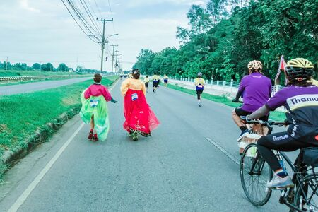KANCHANABURI THAILAND - October 6 : Unidentified Thai women in traditional Korean national costumes run and take photography on the city road on October 6,2019 in Kanchanaburi, Thailand Éditoriale