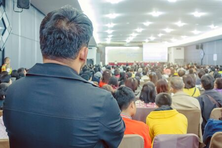 Backside view of spectators standing in a gathering in the back of auditorium full of people. Selective focus.