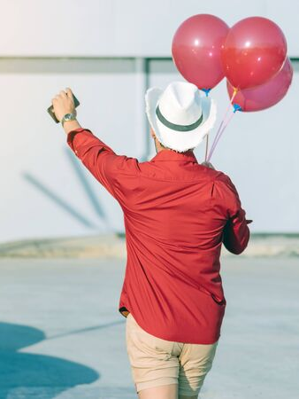 Back view of gay man in red shirt holding red balloons from the car park to join the party in the afternoon. Foto de archivo