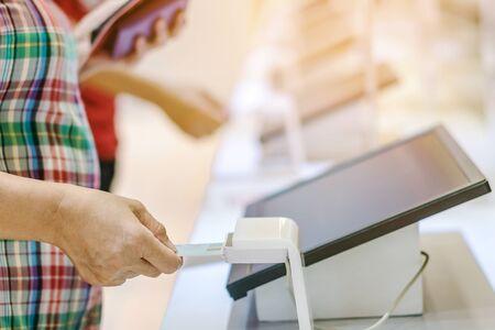 Vicino alla donna usa la carta d'identità inserita nella macchina di verifica dell'identità per ricevere il biglietto per il museo. Messa a fuoco selettiva.