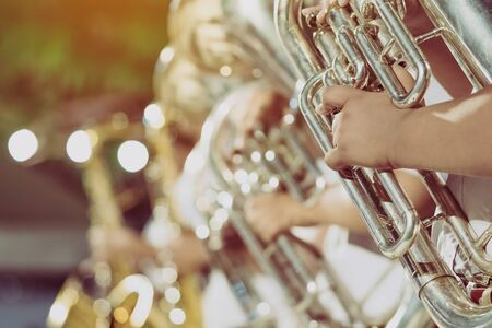 Male student with friends blow the euphonium with the band for performance on stage at night.