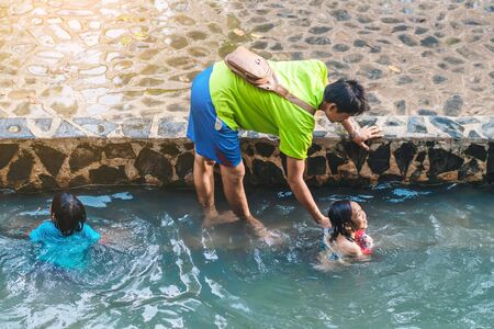 KANCHANABURI, THAILAND - JANUARY 1: Unidentified Asian tourists bathe and soak the body in warm mineral water for good health at Hindad Hotspring on january1, 2020 in Kanchanaburi, Thailand.