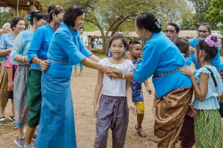 """KANCHANABURI, THAILAND - August 12 : Thai culture's Play """"Ri Ri Khao San"""" playing by trying to catching the last one in the line on street show at local market on august 12,2019 in Kanchanaburi,Thailand. 新聞圖片"""