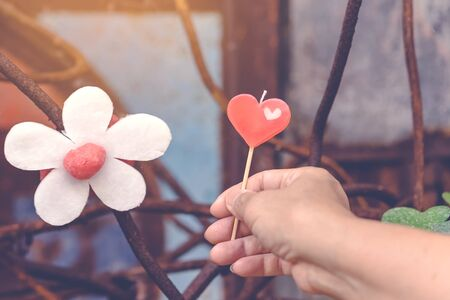 A red heart-shaped candle on woman's hand and an artificial flower made of white and red candles with bluerd image of rusty steel rod in the background.